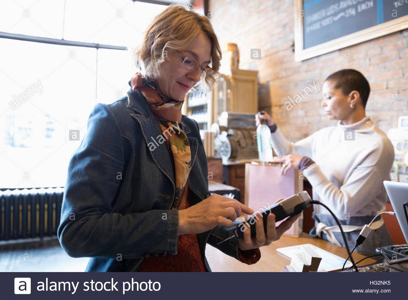 Female customer using pin entry credit card reader at shop counter - Stock Image
