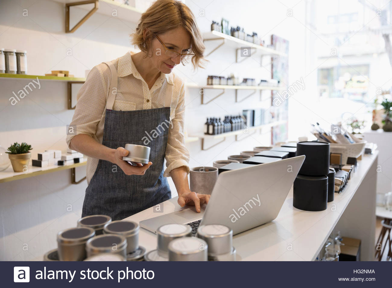 Female home fragrance shop owner working at laptop taking inventory - Stock Image