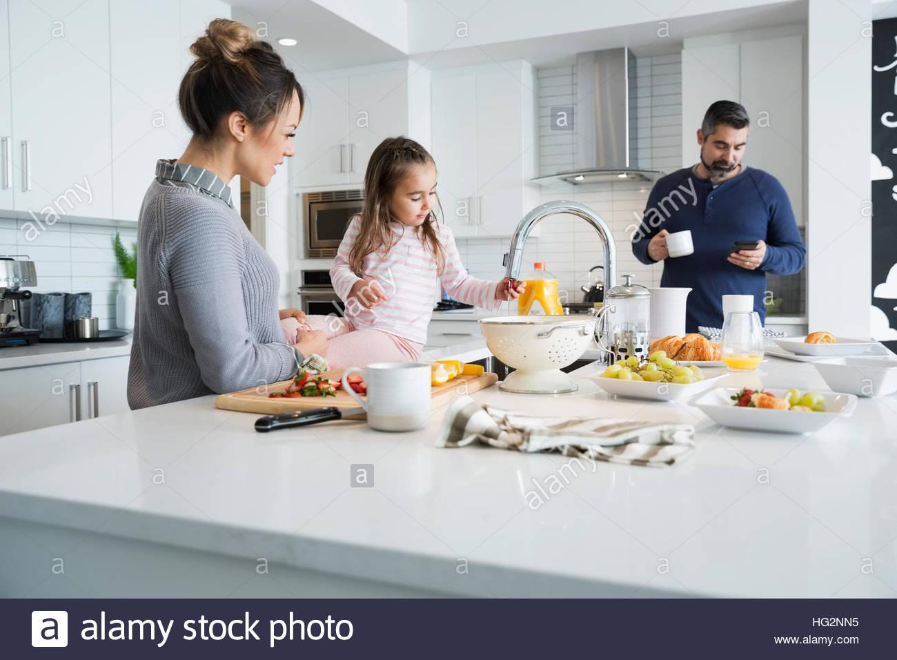 Family preparing breakfast in morning kitchen - Stock Image