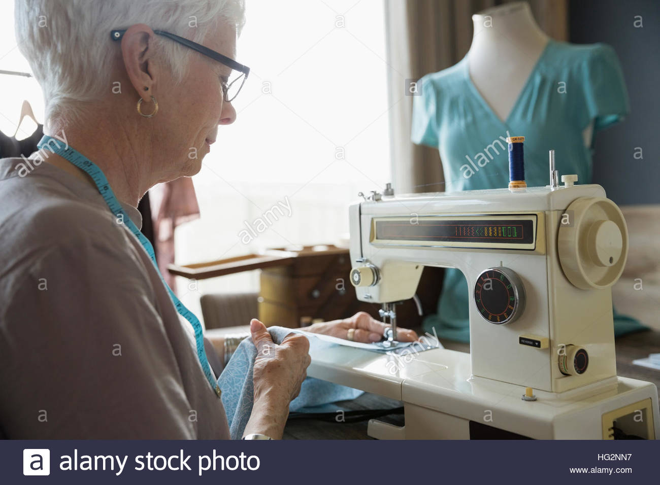 Senior woman seamstress using sewing machine in home office - Stock Image
