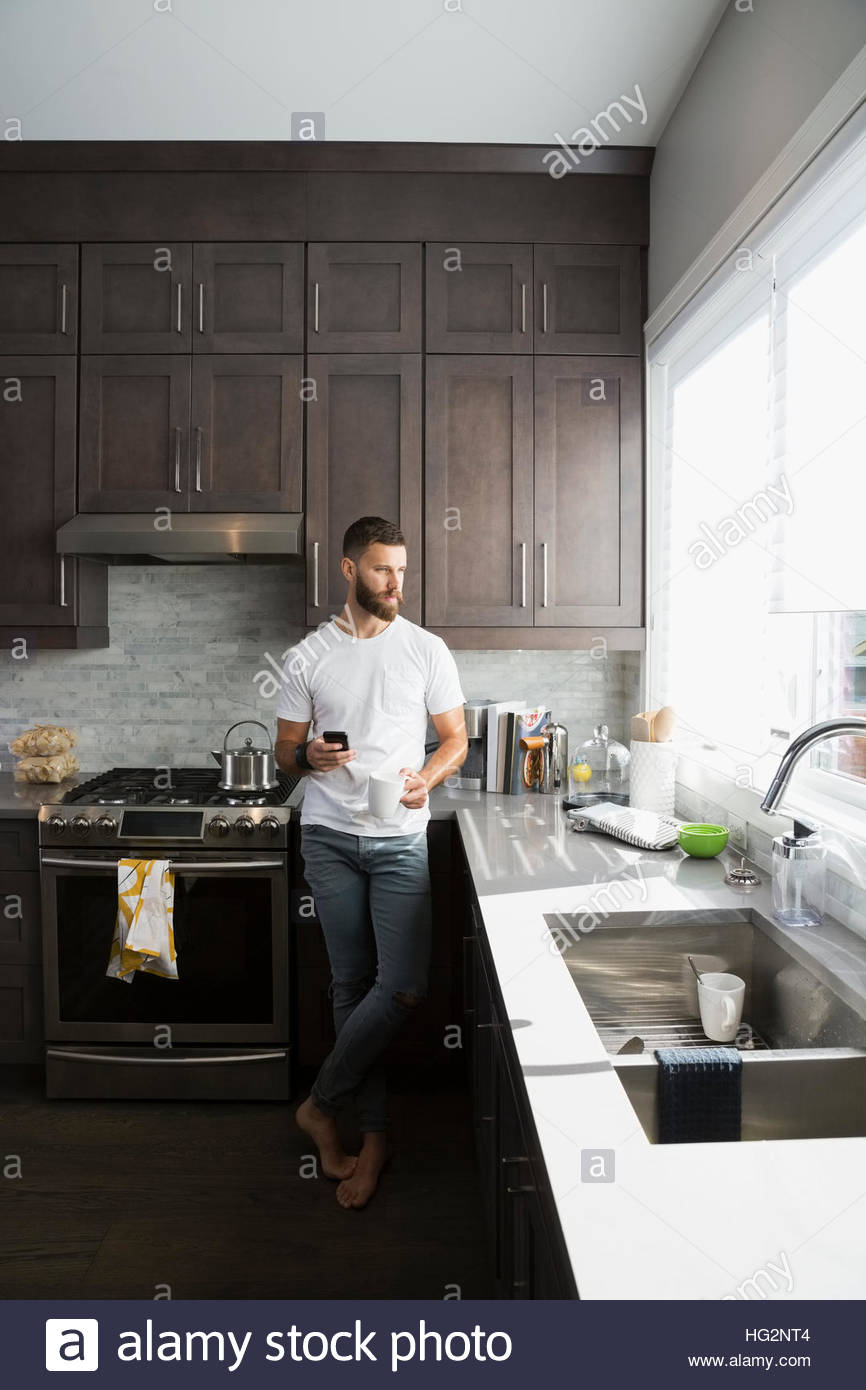 Pensive man drinking coffee and using cell phone in kitchen - Stock Image