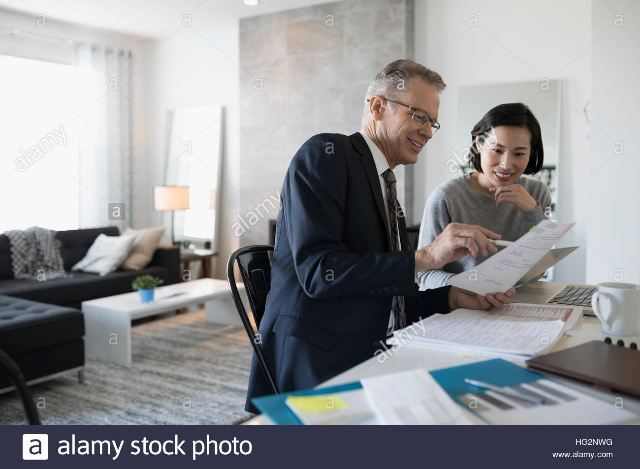 Financial advisor and woman with laptop meeting in dining room - Stock Image