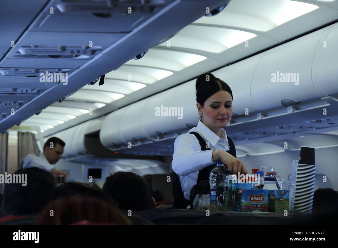 Cabin crew on passenger aircraft attending to passengers needs image in landscape format - Stock Image
