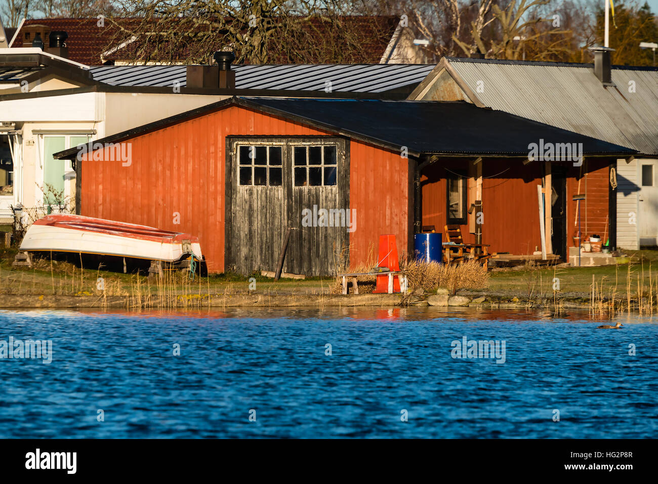 Red wooden boathouse as seen from the sea. Doors closed and small rowboat on land & Wooden Boathouse Hut Shed Stock Photos \u0026 Wooden Boathouse Hut Shed ...