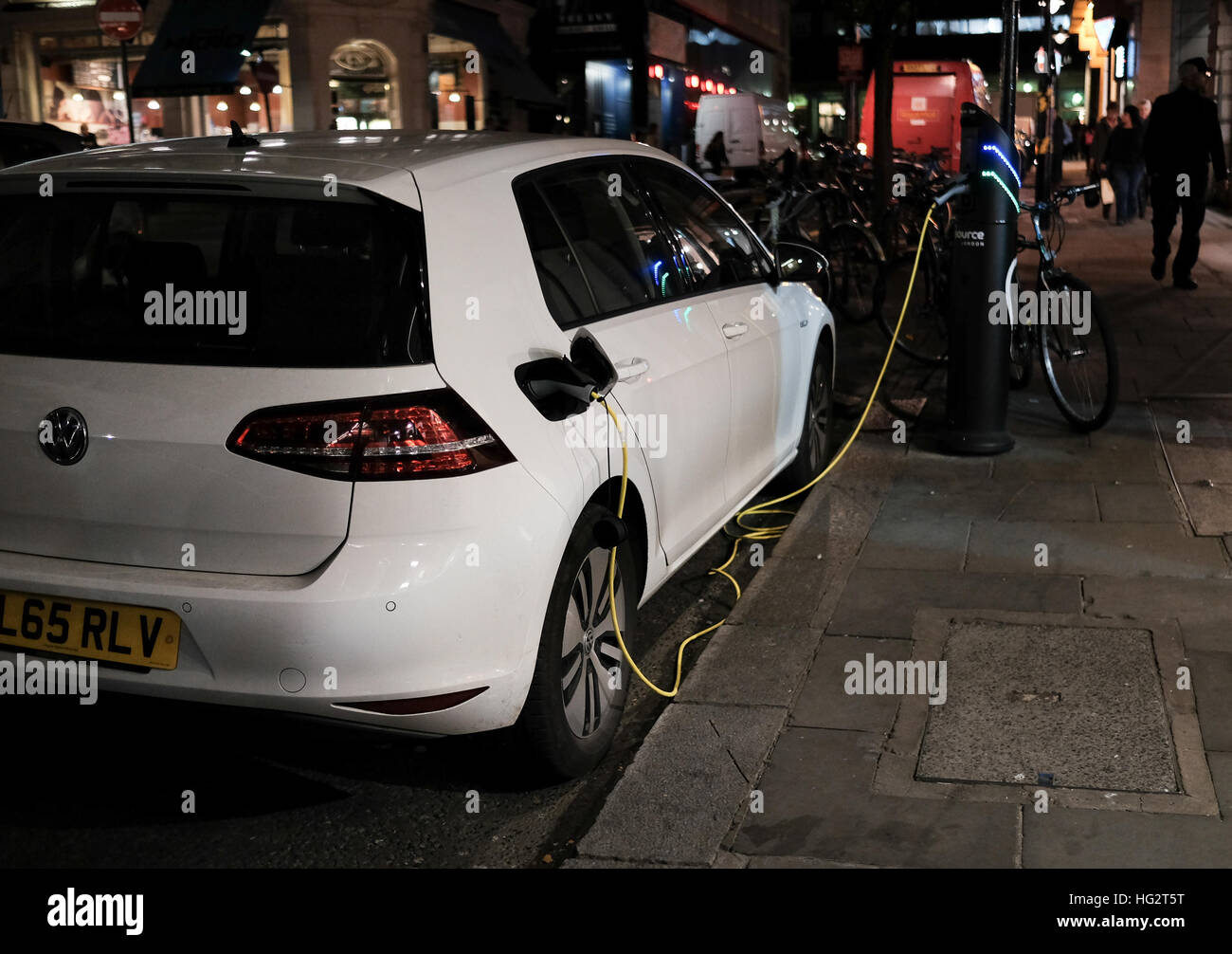An electric VW golf charging on the streets of London at night - Stock Image