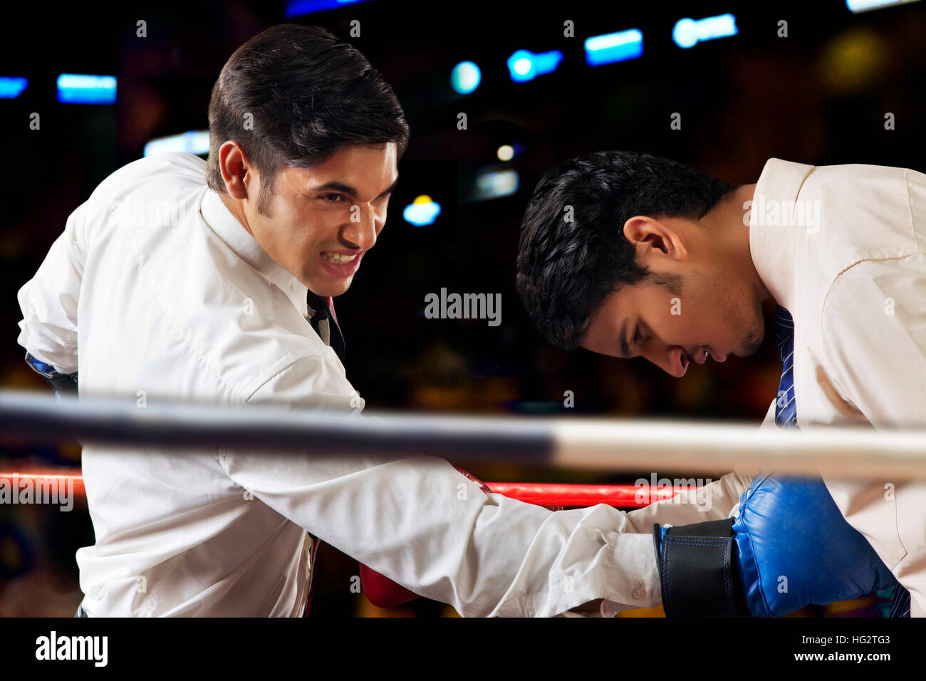 Businessmen fighting in boxing ring - Stock Image