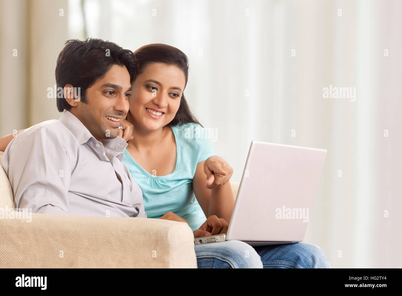 Couple sitting with a laptop - Stock Image