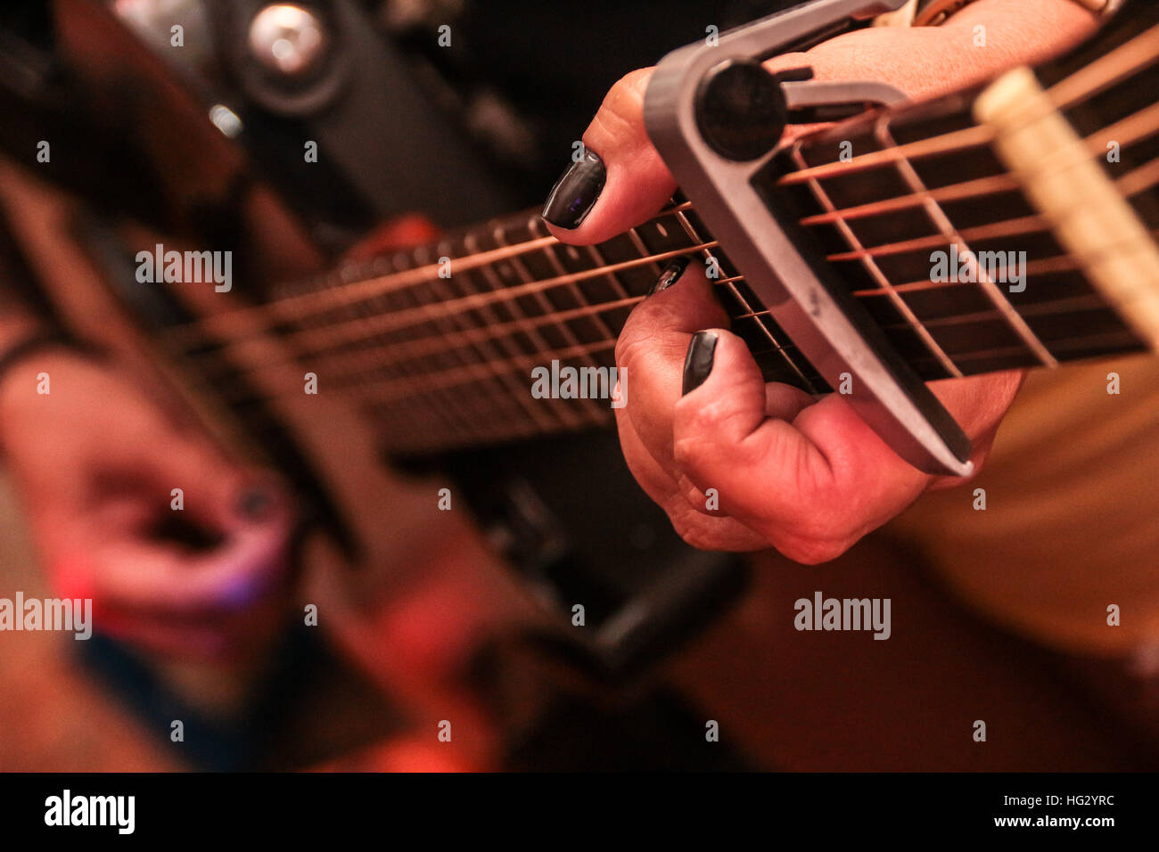 Female hands playing a guitar - Stock Image