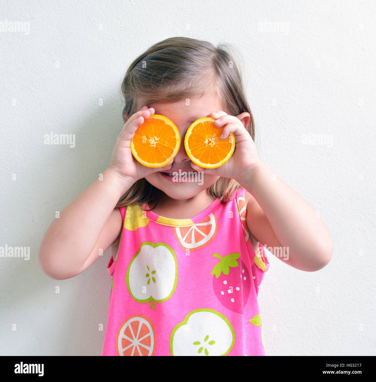 Young girl holding oranges slices over eyes - Stock Image