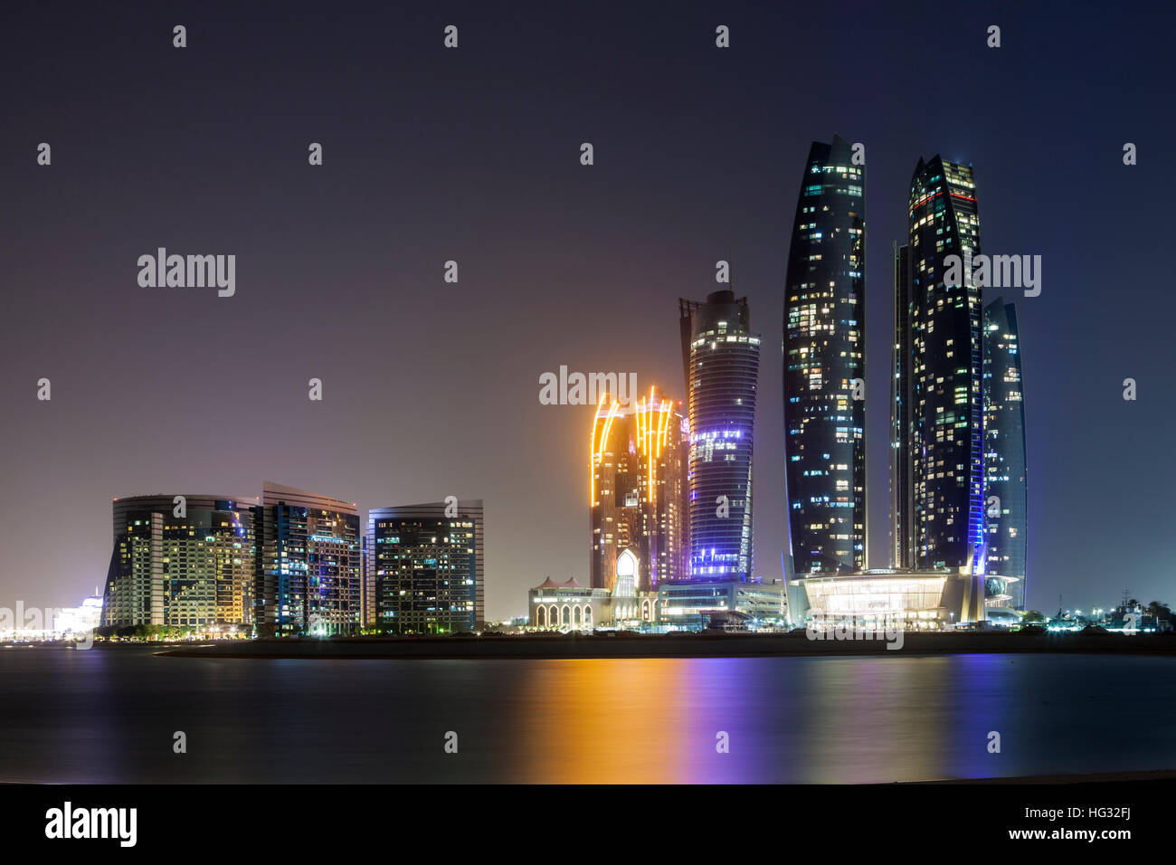 The Etihad Towers in Abu Dhabi illuminated at night - Stock Image