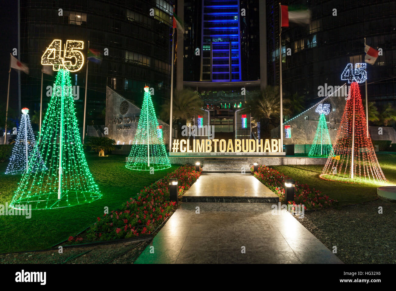 National Day decoration illuminated at night in front of the Etihad Towers in Abu Dhabi - Stock Image
