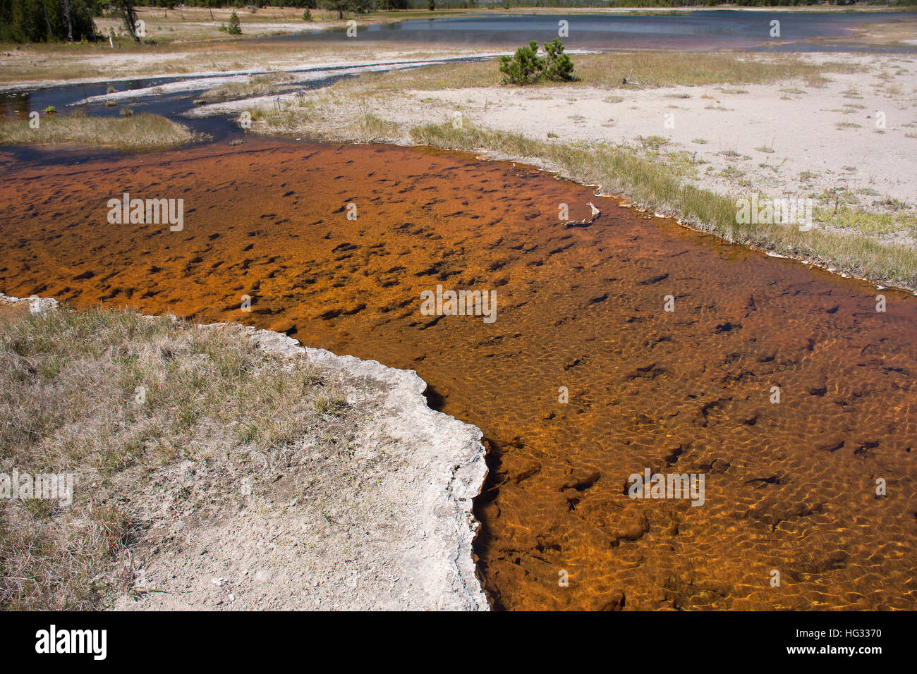 A reddish-orange stream flowing into Hot Lake in Yellowstone National Park. - Stock Image