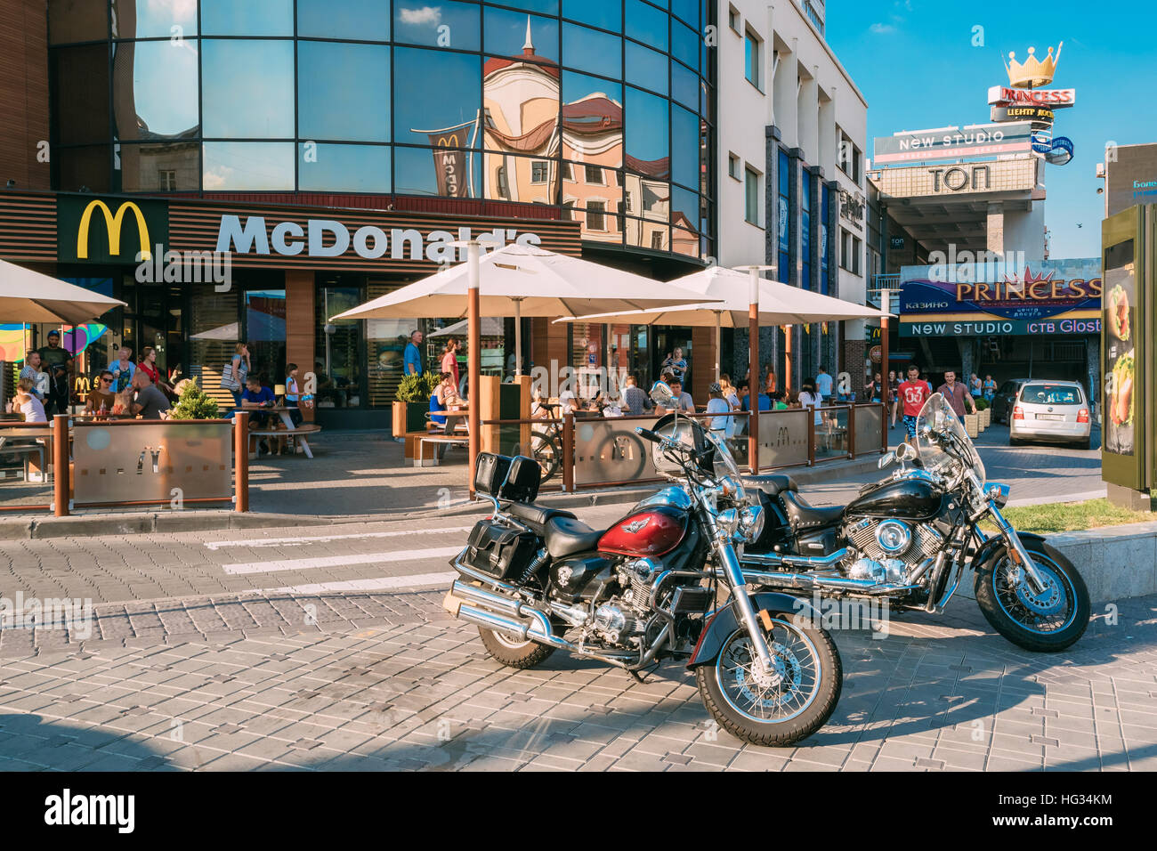 Minsk, Belarus. Two New Chopper Style Motorcycles, Parked Near Crowded Outdoor McDonald's Fast Food Restaurant - Stock Image