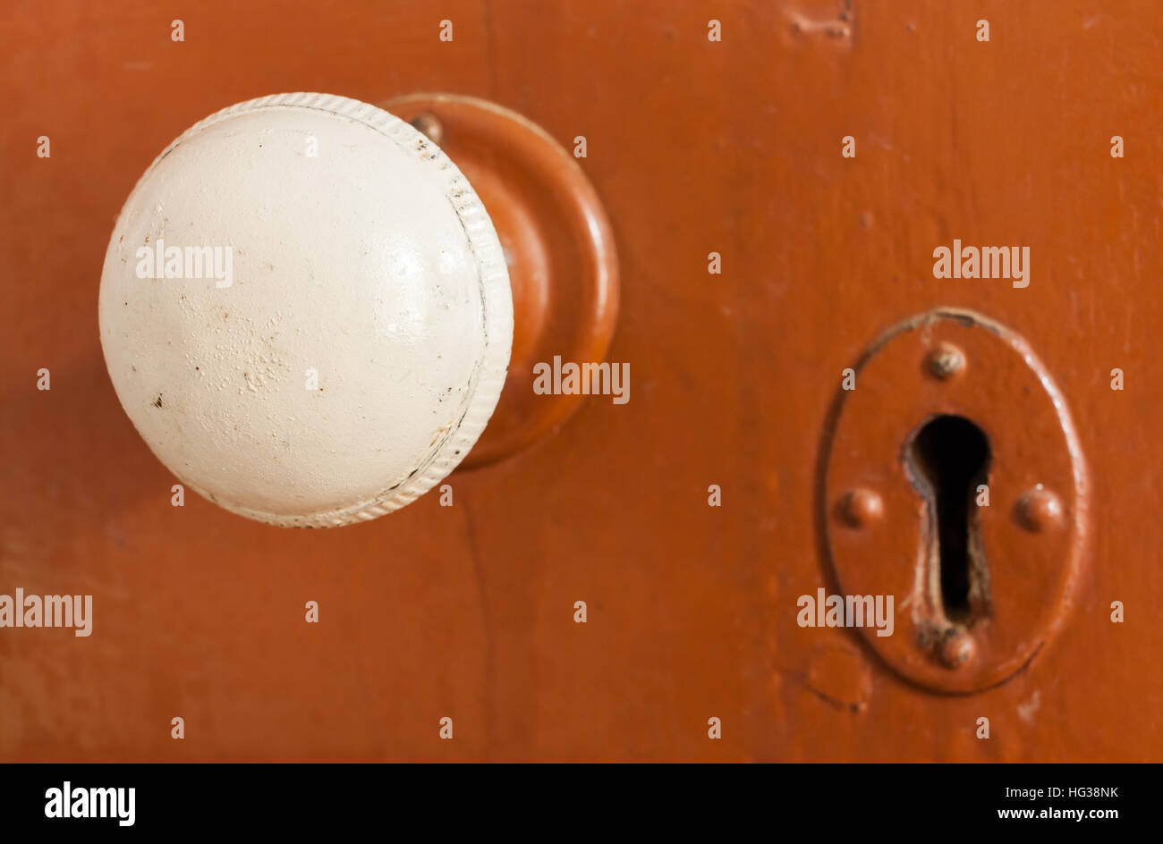 An old white door knob and keyhole on a brown wooden door. - Stock Image