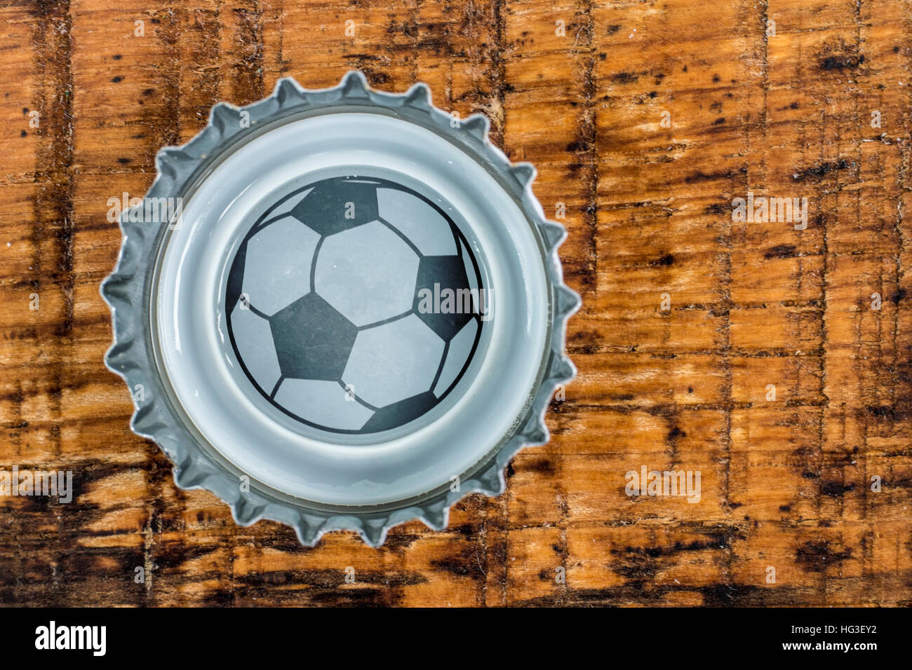Football in a crown cork - Stock Image
