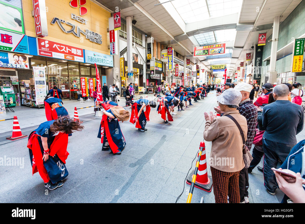 Japan, Kumamoto. Hinokuni Yosakoi festival. Women dance team in line bowing to audience after performance in shopping - Stock Image
