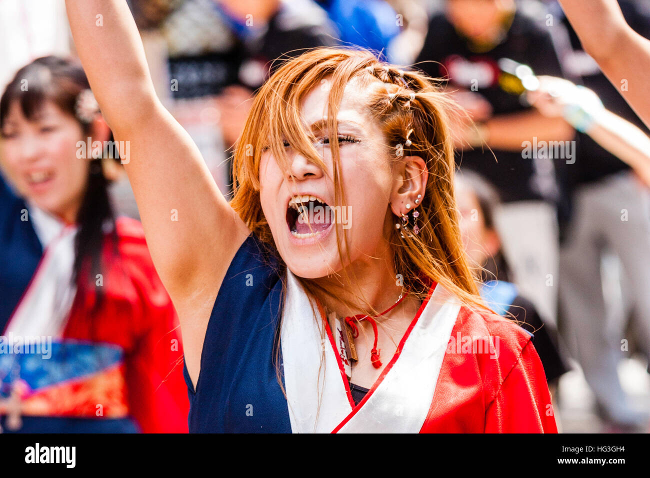 Yosakoi festival. Japanese women dancer with dyed red hair, dancing in city shopping arcade, shouting loudly with - Stock Image