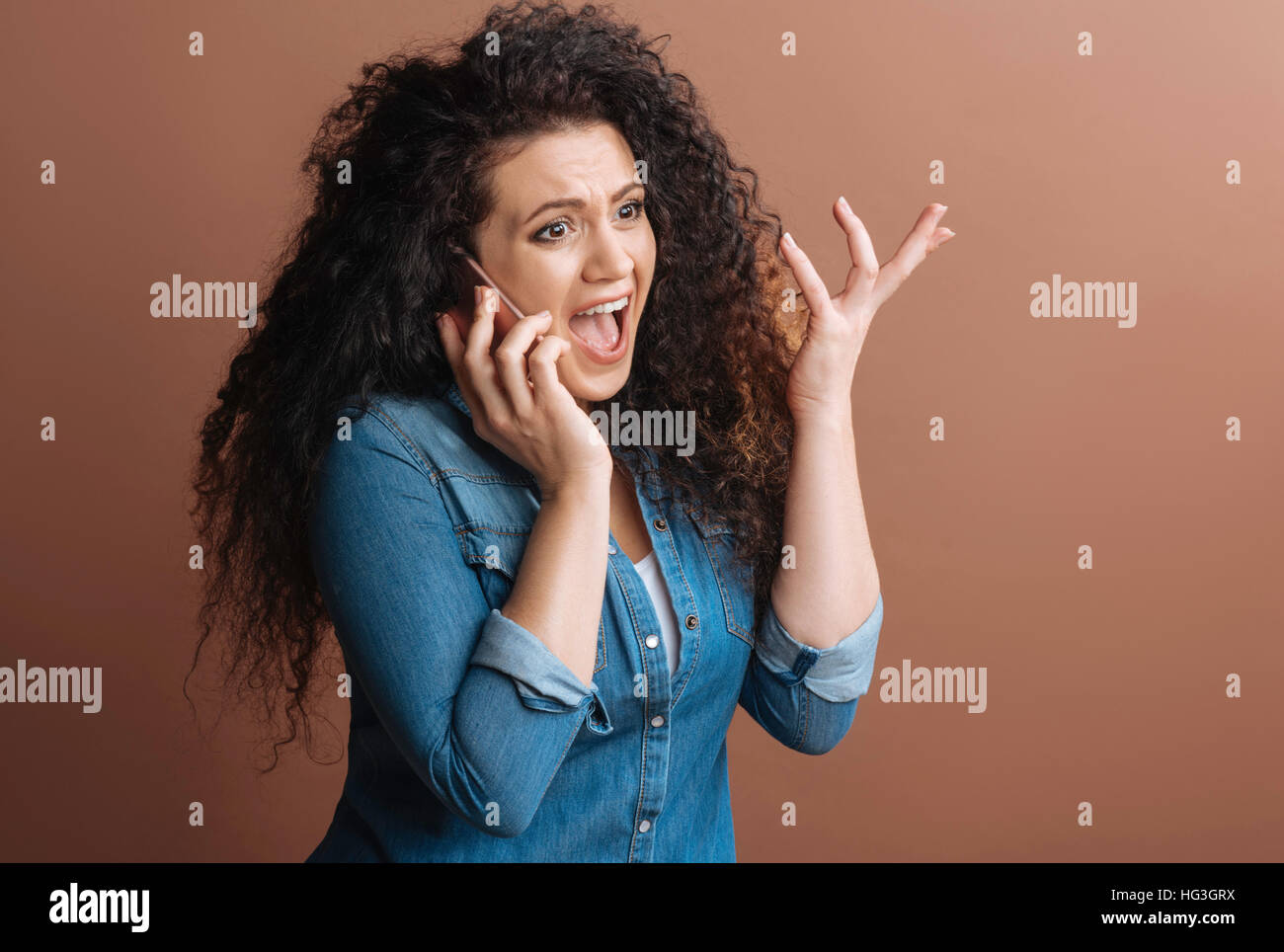 Pretty woman shouting at her conversationalist - Stock Image