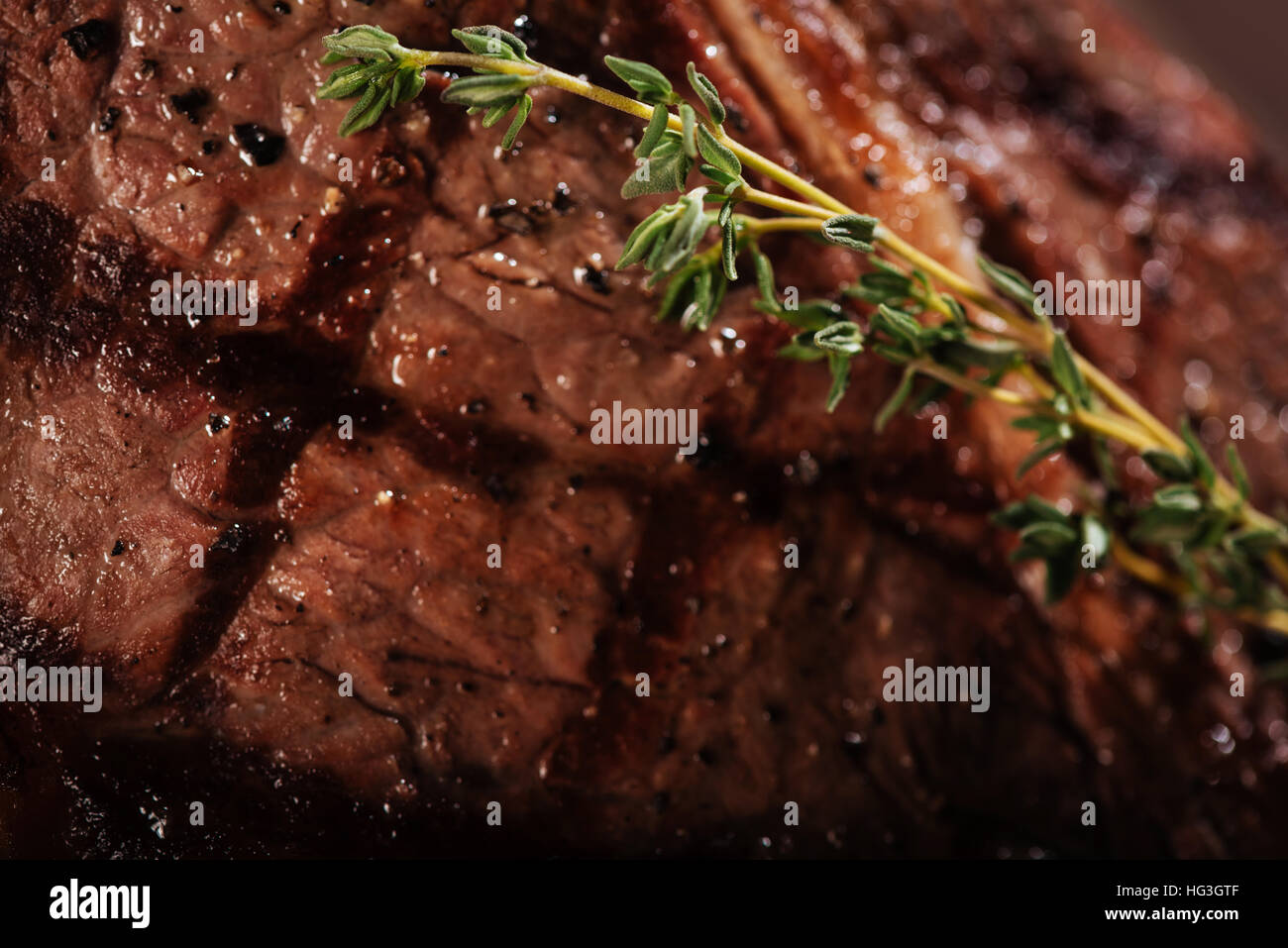Close up of juicy steak being cooked with rosemary - Stock Image