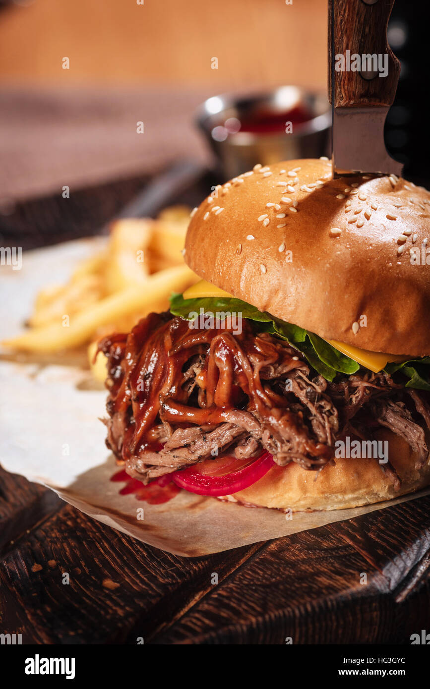Close up of big burger being served in restaurant - Stock Image