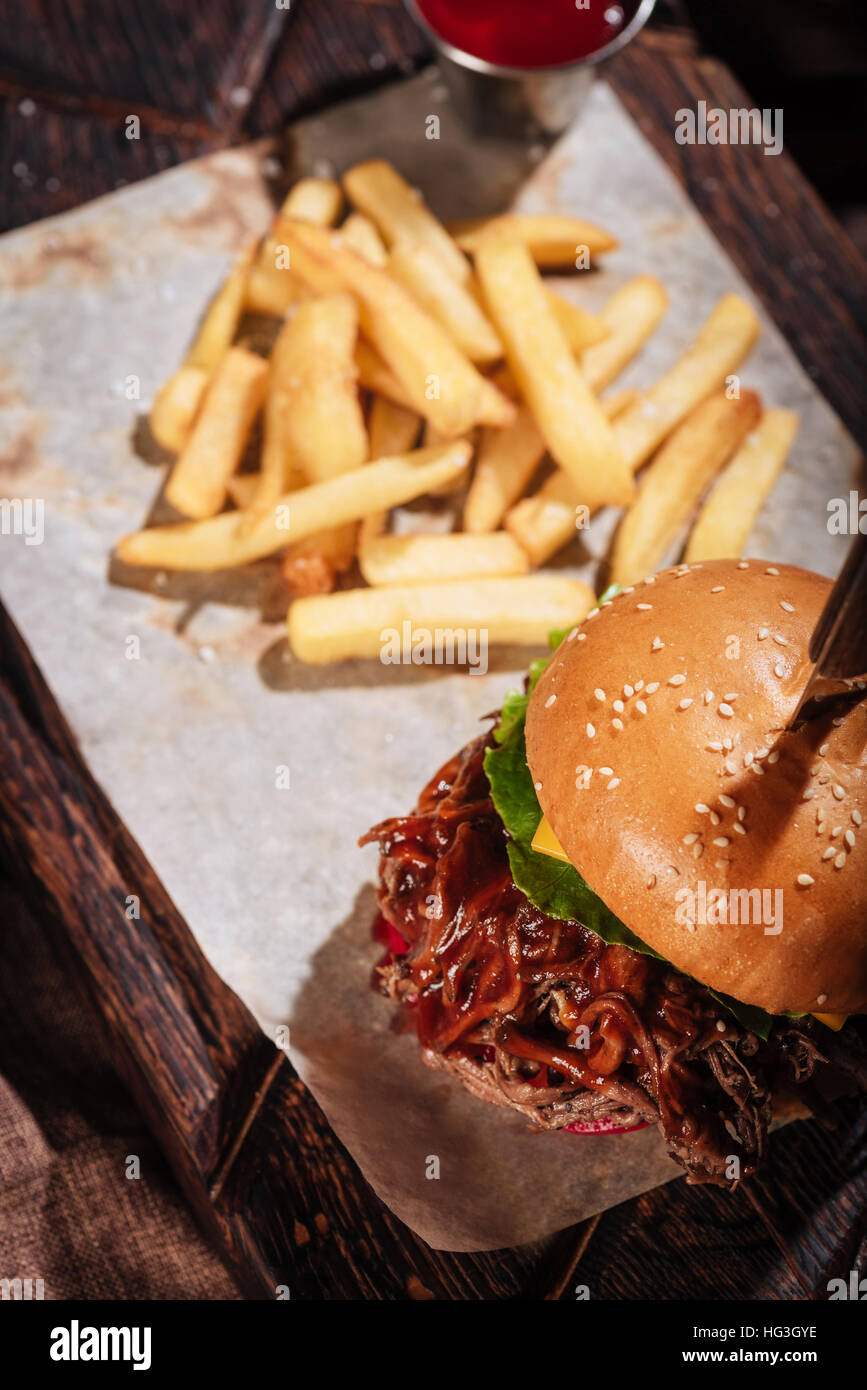 Top view of big burger being served with French fries - Stock Image