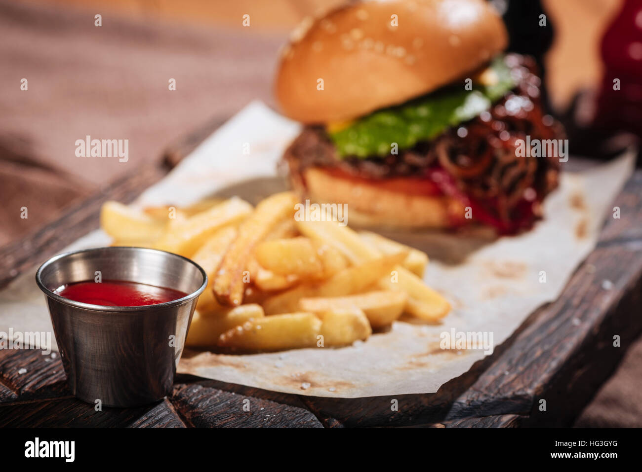 Close up of sauce being served to burger - Stock Image