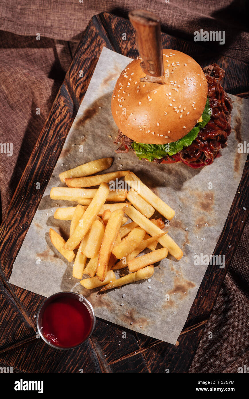 Top view of burger and French fries standing on tray - Stock Image