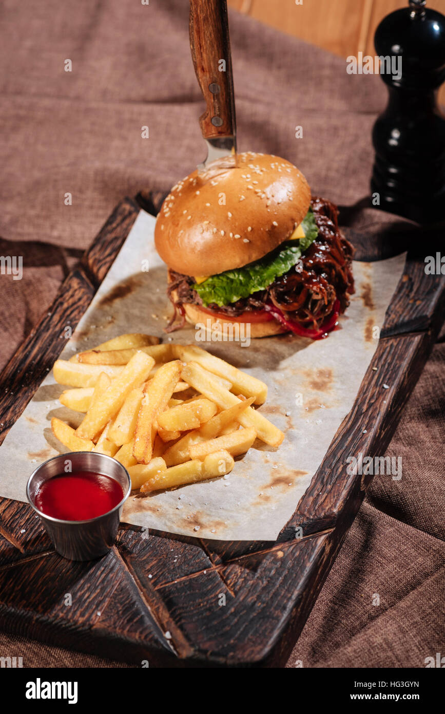Close up of burger and French fries standing on tray - Stock Image