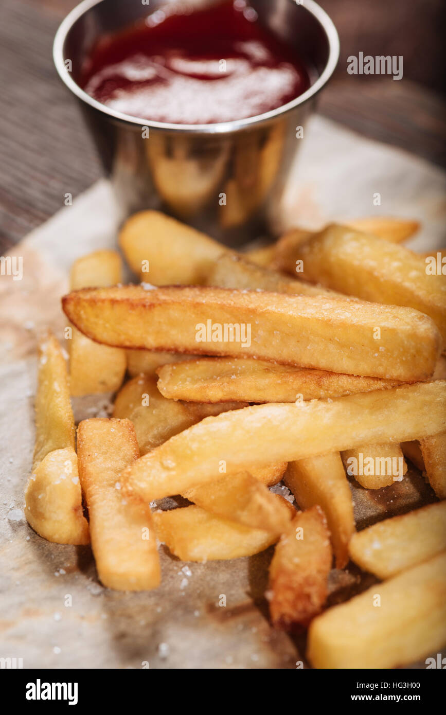 Delighted man salting French fries and burger - Stock Image
