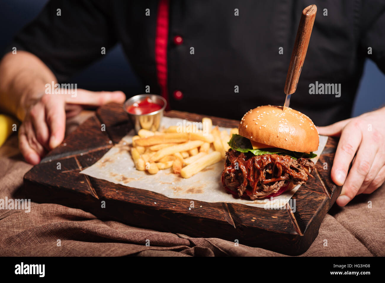 Happy man holding a tray with burger and French fries - Stock Image