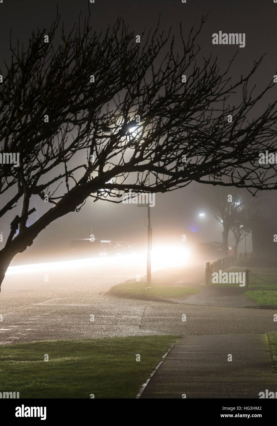 Residential road with a car going past in foggy weather at night. Foggy weather. Mist at night. Fog at night. - Stock Image