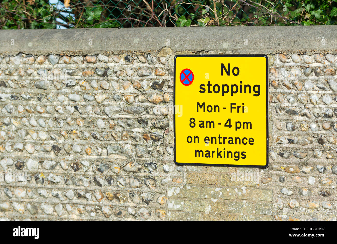 No stopping sign attached to a wall in the UK. - Stock Image