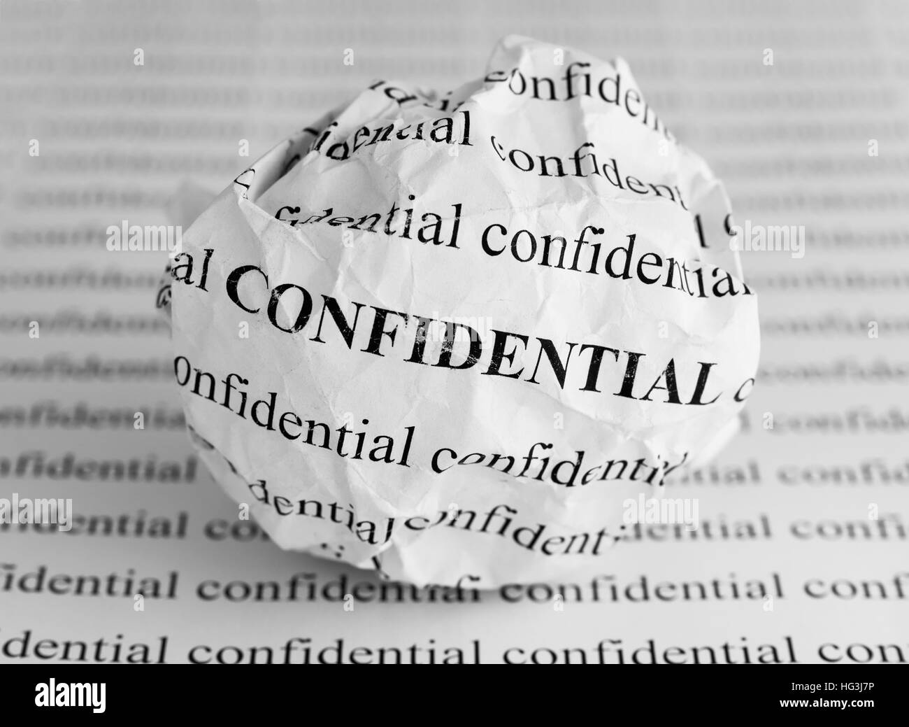 Crumpled paper ball with words Confidential. Black and white. - Stock Image
