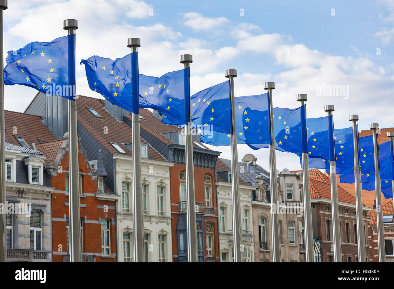 A line of EU flags flying on metal poles in front of the Berlaymont Building in Brussels with traditional houses - Stock Image