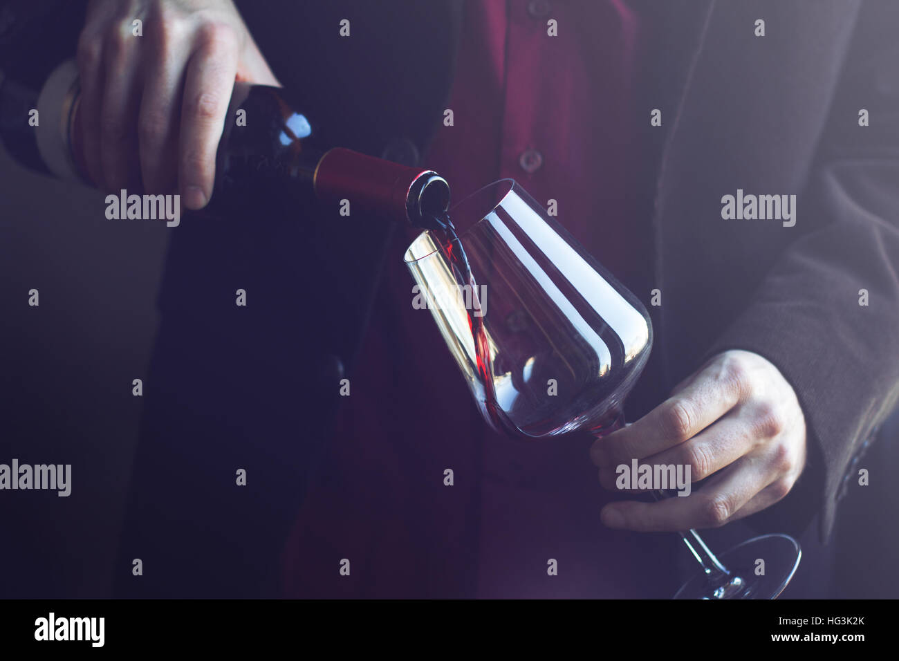 Horizontal close up of Caucasian man in black suit and shirt pouring red wine into a tall glass in a bar - Stock Image
