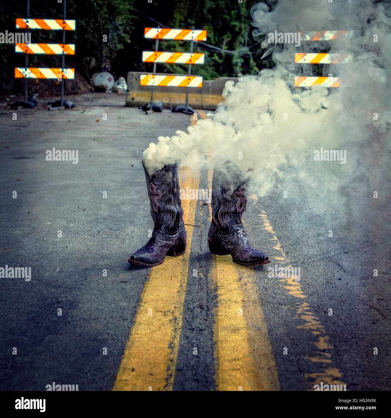 A pair of  smoking cowboy boots in front of road construction on a double yellow line - Stock Image