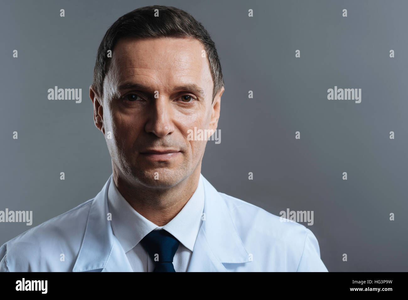 Handsome doctor posing on a grey background - Stock Image