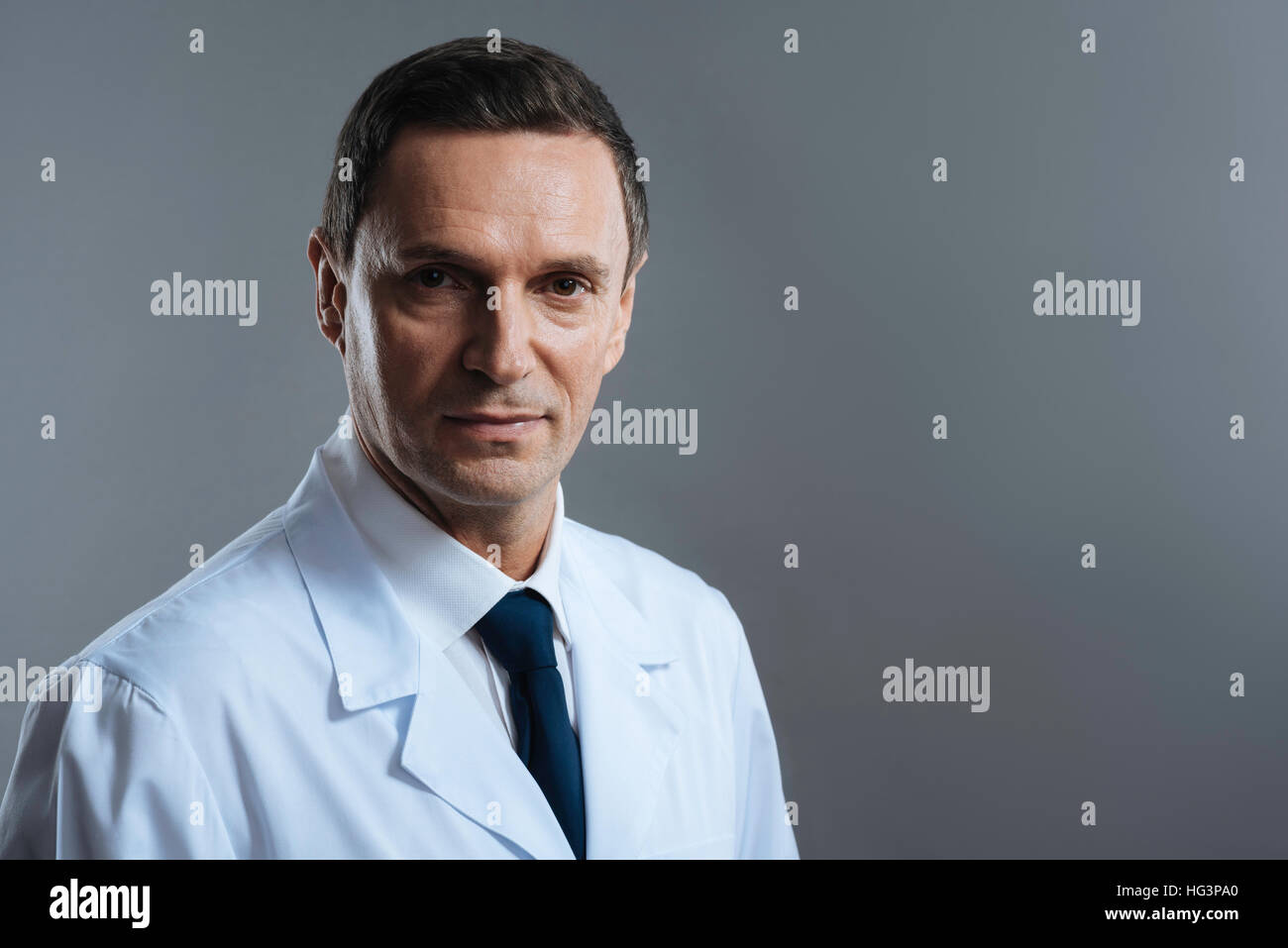 Portrait of a doctor standing on grey background - Stock Image