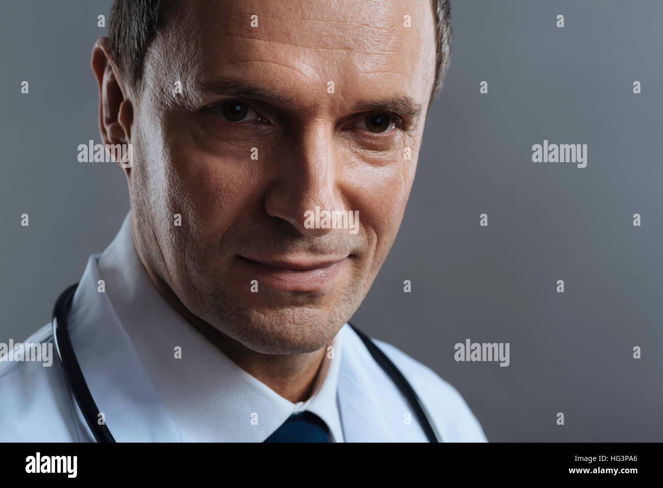 Close up of a doctor standing on grey background - Stock Image