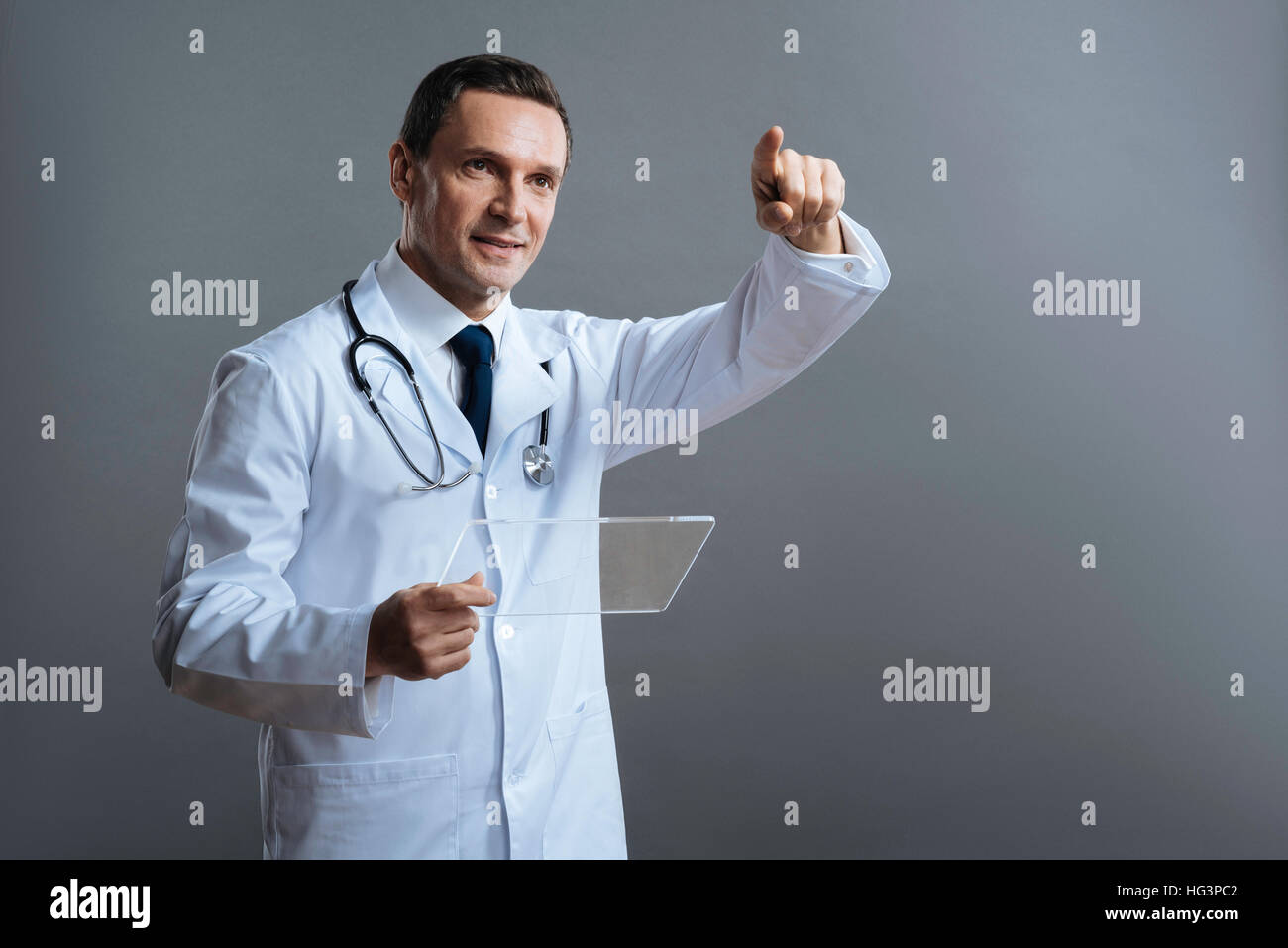 Delighted doctor pointing somewhere with his finger - Stock Image