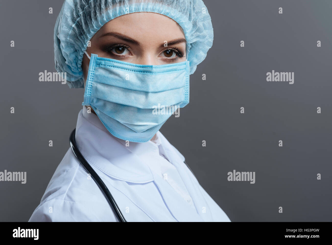 Female doctor gesturing on grey background - Stock Image