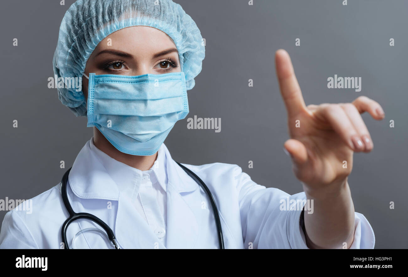 Close up of pretty woman wearing medical face mask - Stock Image