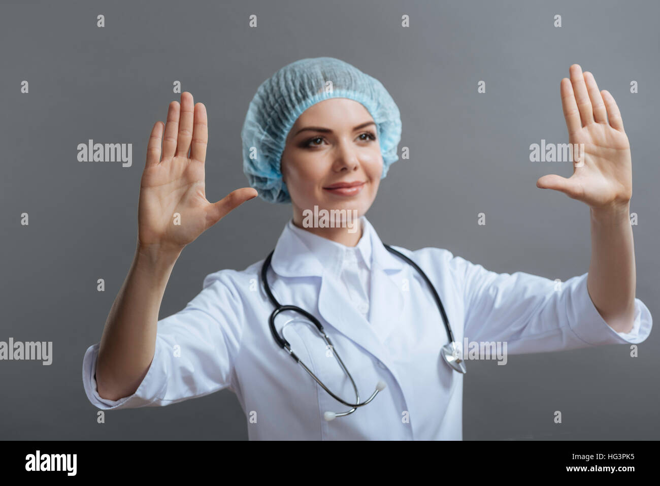 Female doctor putting hands up on grey background. - Stock Image