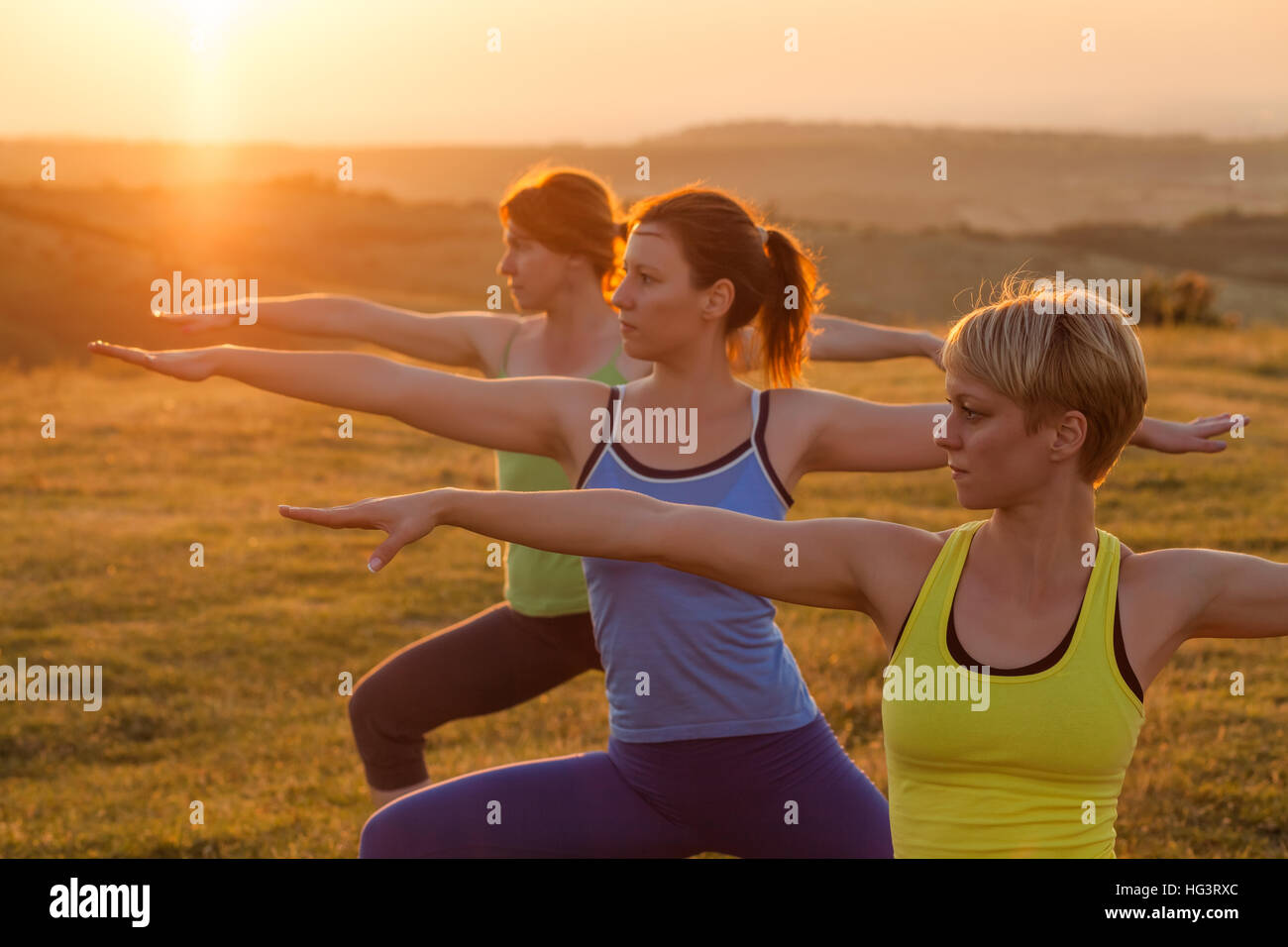 Three girls are practicing yoga in sunset. Warrior position. - Stock Image