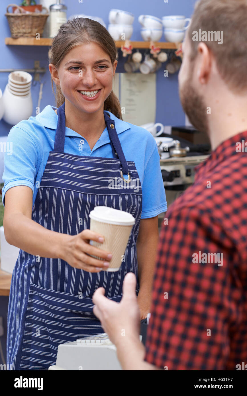 Female Cafe Worker Serving Customer With Takeaway Coffee - Stock Image