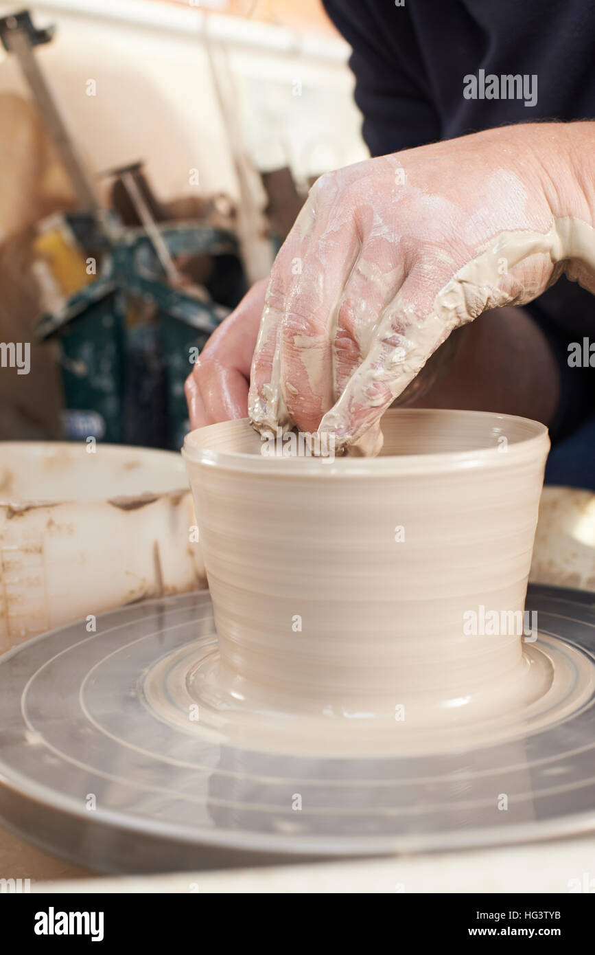 Close Up Of Potter Moulding Clay On Wheel Stock Photo