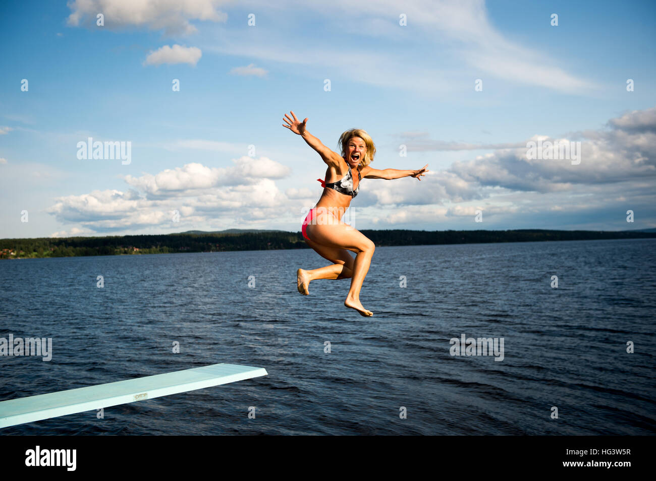 Woman jumping off diving board into lake - Stock Image