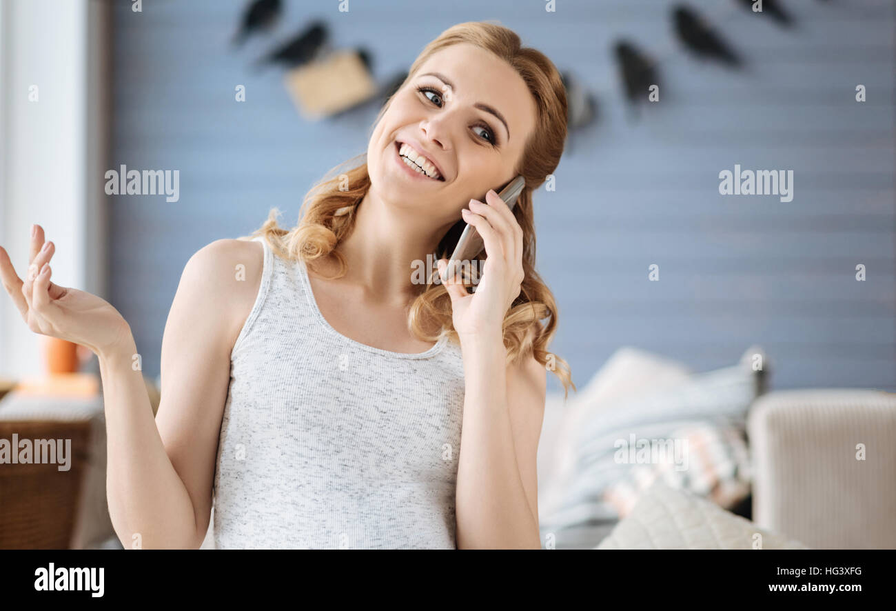 Pregnant woman using cellphone in bedroom - Stock Image
