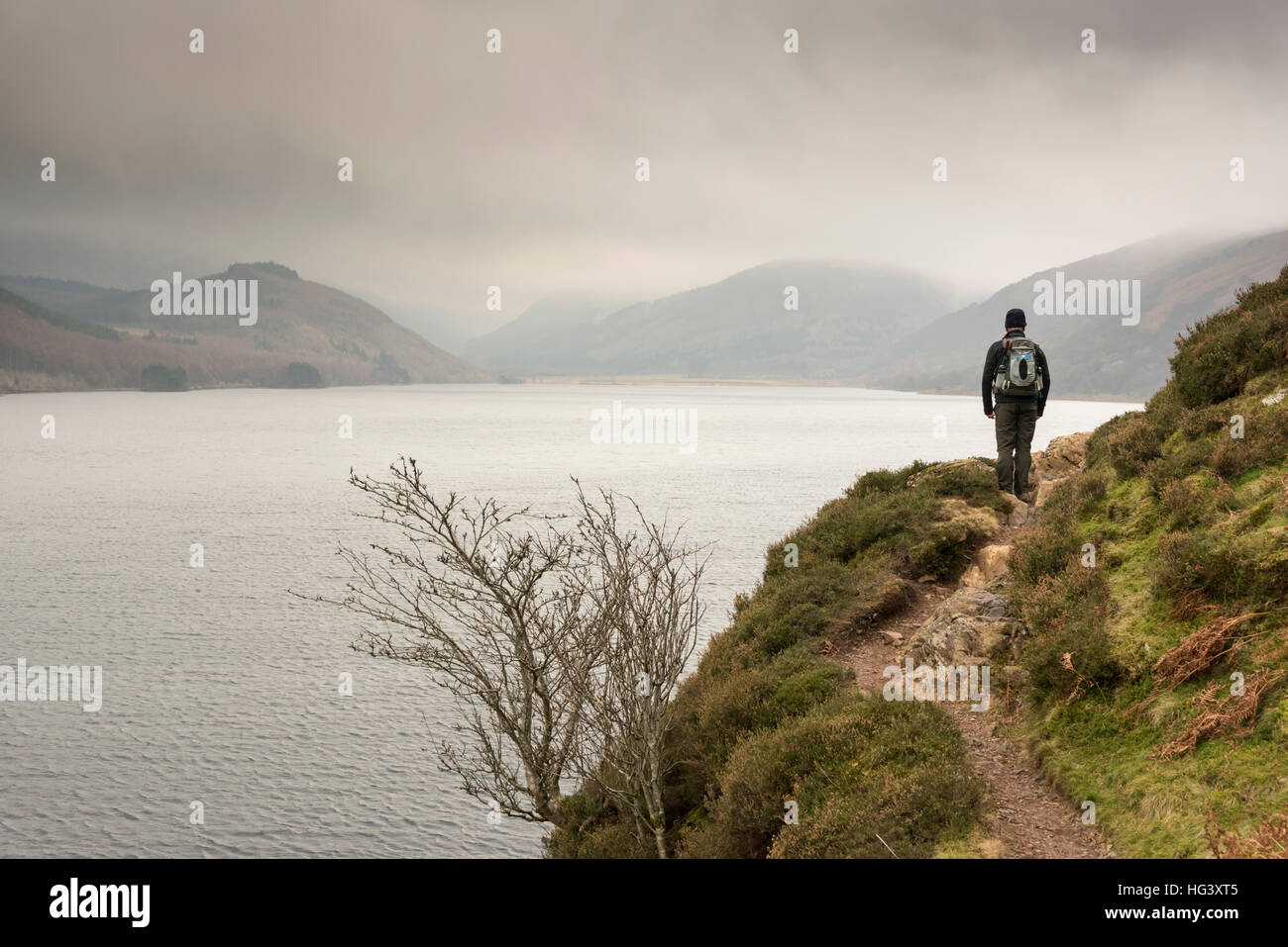 A man hill walking in the Lake District Cumbria UK on the shore of Ennerdale in overcast winter weather - Stock Image