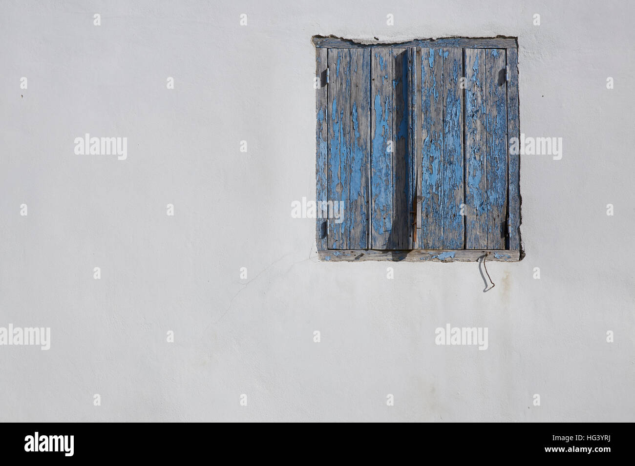 Paphos, Cyprus. White wall, window with light blue shutters. - Stock Image